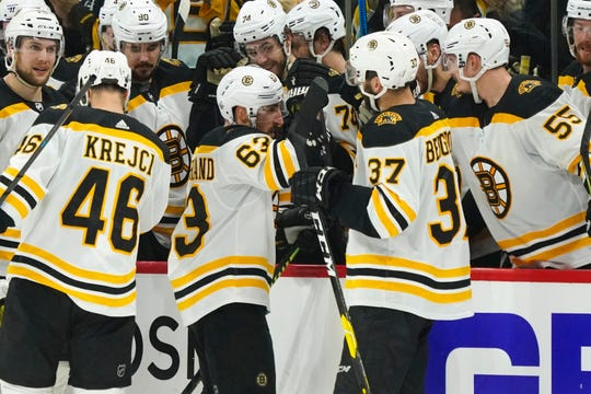 Bruins left wing Brad Marchand (63) celebrates with center Patrice Bergeron (37) after scoring a goal against the Hurricanes during the conference final.