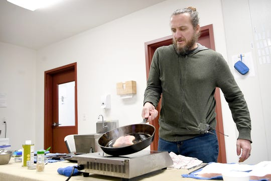 "Gavin Baker works with a sturgeon filet in a pan in a makeshift kitchen he brought with him to Marshallberg Farm as he takes a tour of the facility on March 7, 2019. ""One of the things I want to do with this menu is bring some things to the kitchen and to the market that aren't currently represented,"" he said about the new Noble Cider restaurant, The Greenhouse."