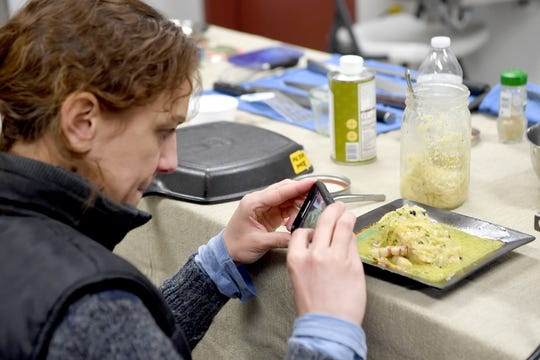Sabine Mader takes a cell phone photo of one of the pieces of sturgeon cooked by Gavin Baker in his makeshift kitchen he brought to Marshallberg Farm as he takes a tour of the facility on March 7, 2019.
