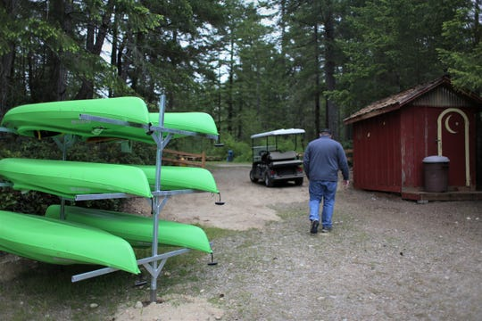 Scotty Jackson, executive director of Camp Lake Helena, walks past the new canoes ready to be paddled around by summer day campers.