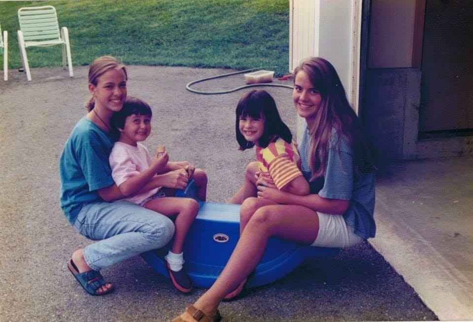 Emily Welch, left, sits on her sister Kristin Long's lap with two of their other sisters.