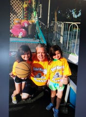 Bob Durant gets help from his granddaughters, Angela Ervin, 9, and Grace Ervin, 7 at a carnival basketball game. Durant has become active in Williamstown's Our Lady of Peace Parish since becoming a Catholic three years ago.