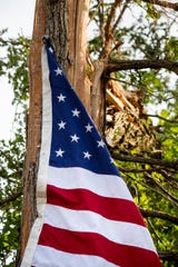 Dean Sutter and his brother nailed an American flag into a tree in his front yard, after a tornado destroyed his flagpole in Brookville, Ohio, on Tuesday.