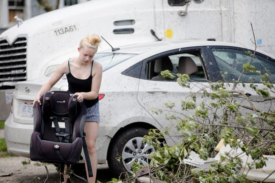 Sally Roberts cleans off her niece's car seat while helping her sister on Dixie Highway in Dayton, Ohio, on Tuesday, May 28, 2019.