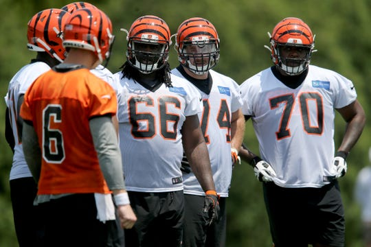 Cincinnati Bengals center Trey Hopkins (66), guard Keaton Sutherland (74) and guard O'Shea Dugas (70) listen to Cincinnati Bengals quarterback Jeff Driskel (6) in the huddle during Cincinnati Bengals organized team activities practice, Tuesday, May 28, 2019, at practice fields next to Paul Brown Stadium.