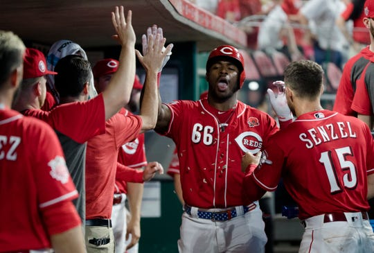 Cincinnati Reds right fielder Yasiel Puig (66) celebrates with his teammates after hitting a home run in the seventh inning of the MLB National League game between Cincinnati Reds and Pittsburgh Pirates at Great American Ball Park in Cincinnati on Monday, May 27, 2019.