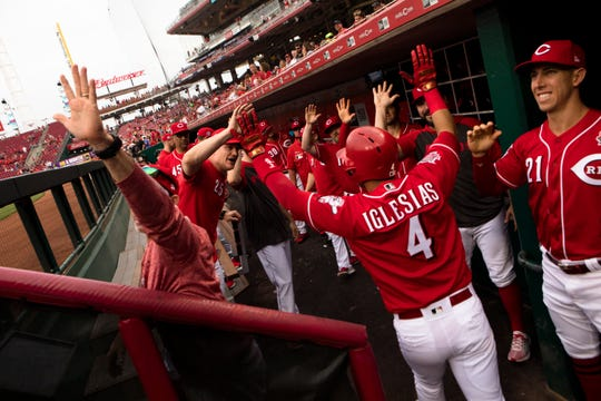Cincinnati Reds shortstop Jose Iglesias (4) celebrates with teammates after hitting a grand slam in the first inning of the MLB National League game between Cincinnati Reds and Pittsburgh Pirates at Great American Ball Park in Cincinnati on Monday, May 27, 2019.