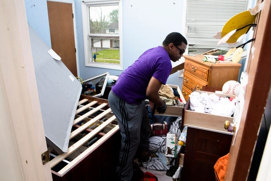 Drew Goodall removes clothes from a room in his mother's home in the Westbrook neighborhood in Dayton, Ohio, on Tuesday, May 28, 2019. A tornado struck the neighborhood the night before.