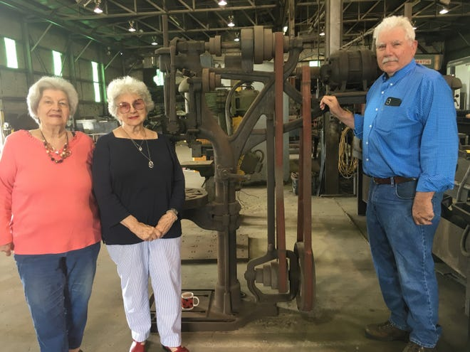 Standing alongside a circa 1940s drill press up for auction Thursday  at Langford's Welding and Steel Works are the sibling ownership trio of Katherine Key, left, Carolyn Lyle and Tom Langford.