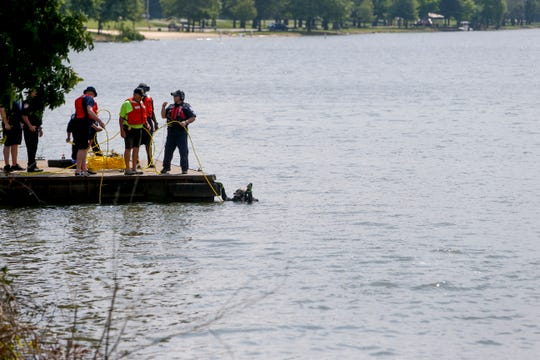 Divers surface at a boat dock to speak to other first responders in the ongoing rescue or recovery attempt of a drowning victim along the Cumberland River near Chapmansboro, Tenn., on Tuesday, May 28, 2019.