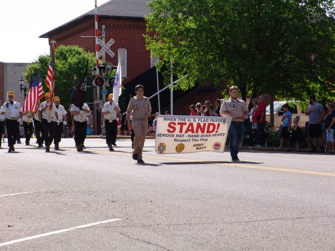 Boy Scouts carried a banner asking people to show respect to the flag as it passed by during the annual Memorial Day parade.