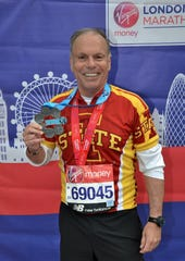 Ron Hankins holds up his Abbott award after finishing the London Marathon in April.