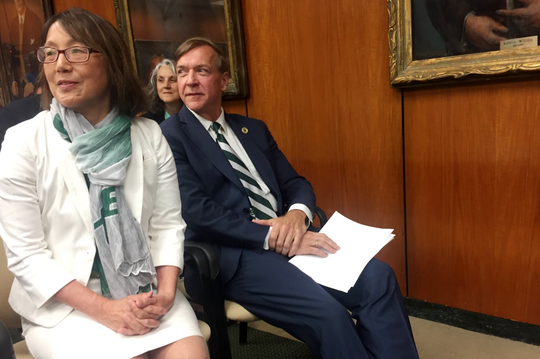 Samuel Stanley and his wife, Dr. Ellen Li, sit in the audience while the Michigan State University board approves his hire on Tuesday, May 28, 2019.