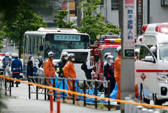 A school bus, center, is parked at the scene of an attack in Kawasaki, near Tokyo Tuesday, May 28, 2019.