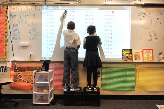 Kimari Barden (left), 7, and Nakeya Beberly, 7, work on their addition problems projected on a dry erase board in the classroom of teacher Pamara English at Brenda Scott School in Detroit on April 21, 2013.