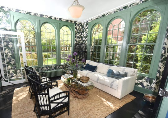The solarium in Erica and Travis Harrison's home in Detroit's Indian Village neighborhood features a sophisticated botanical wallpaper from House of Hackney. The trim is painted a custom shade of green created by Benjamin Moore, taken from a paint chip from an old building in Detroit that Erica fell in love with.