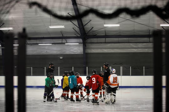Malakye Johnson (1) gathers with his teammates during a Snider Hockey practice at the Scanlon Ice Rink in Philadelphia. The Philadelphia-based Snider Hockey organization named after the late Flyers owner now has more than 3,000 kids in its program and almost a third are girls. Snider Hockey officials want to get to a point that boys and girls are split 50-50, and a new endeavor with the Howe Foundation is another step toward that goal.