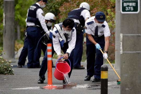 Police officers clean the scene where a man wielding a knife attacked commuters May 28, 2019, in Kawasaki, near Tokyo.
