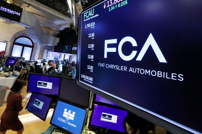 The Fiat Chrysler Automobiles logo appears above a post on the floor of the New York Stock Exchange on Tuesday. Fiat Chrysler is proposing a merger with French carmaker Renault aimed at saving billions of dollars for both companies.