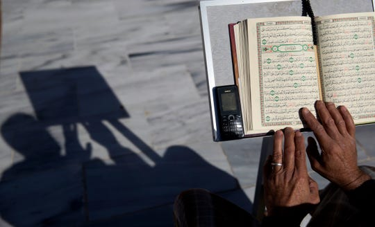 A Palestinian reads verses of the Quran, Islam's holy book, during the month of Ramadan at Al Emari Mosque in Gaza City.