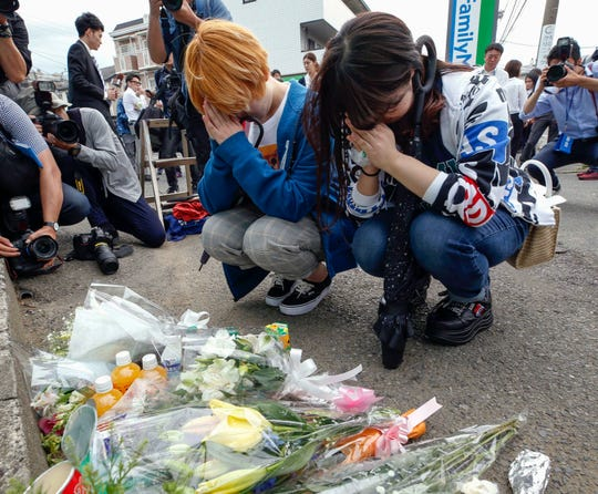 Women pray after offering flowers near the scene where a man wielding a knife attacked commuters in Kawasaki, near Tokyo Tuesday, May 28, 2019.