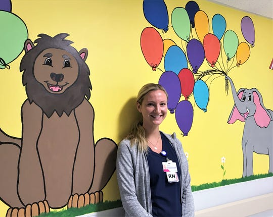 Abigail Clark, a registered nurse in the pediatric unit at Arnot Ogden Medical Center, shows off one of the murals painted in the unit by members of the Elmira College Art Club.
