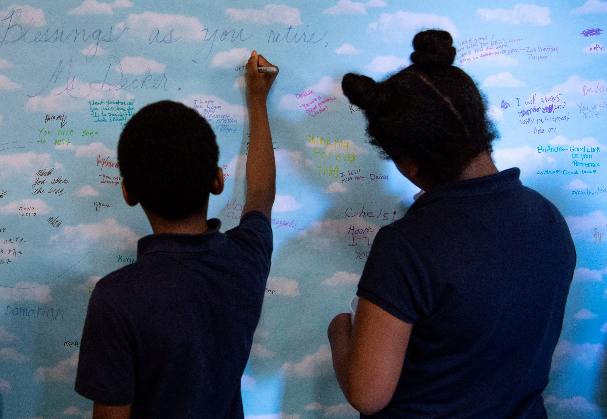 """Joshua Academy students sign a cloud-covered wall-hanging that read, """"Blessings as you retire, Ms. Decker"""" at her retirement party on the last day of school Thursday, May 24, 2019."""