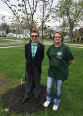 A Oak Harbor Middle School Student Council member and Tree Commission chairwoman Marie Darr stand in front of the recently planted Legacy Sugar Maple tree. The tree is in front of the Oak Harbor Middle School. It is dedicated to all retired teachers.