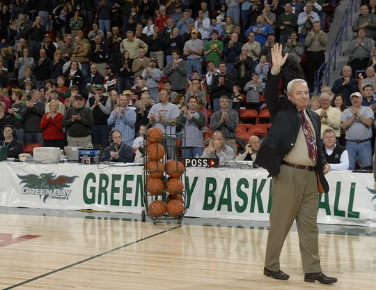Former UWGB coach Dick Bennett waves to the crowd after being honored at halftime of a game in 2008, when it was announced the practice court at the Kress Events Center would be named after him.