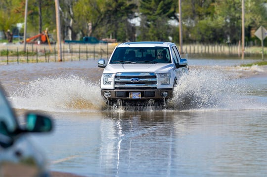 Motorist navigate flood water running over Highway 200 in the town of Sun River, Tuesday. Additional flooding was forecast by the National Weather Service in Great Falls in the Sun River area and waters are expected to remain above flood stage through next Tuesday.