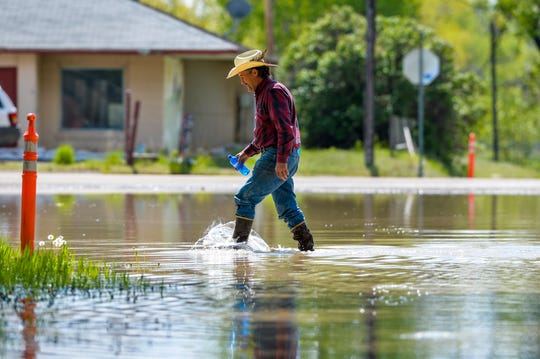 Bruce Lee wades through floodwaters Tuesday in Sun River.