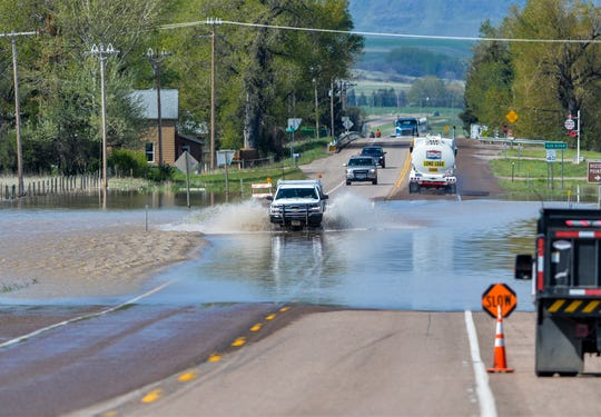 Motorists navigate high water crossing Highway 200 in the community of Sun River, one of the communities impacted by flooding of the Sun River.