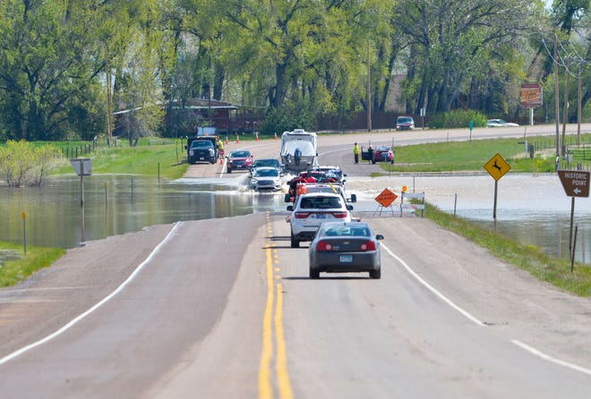 Flood water  from the Sun River runs over Highway 200 in the town of Sun River, Tuesday.  The Sun River rose to about 9 feet Tuesday after the most recent storm dropped 3 to 6 inches of rain along the Rocky Mountain Front.