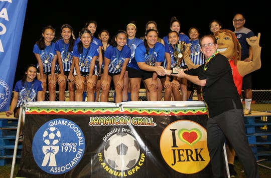 : Jamaican Grill's Frank Kenney presents the Jamaican Grill Women's GFA Cup champion trophy to Nikkie Paulino and the Guam Shipyard women's team during a short awards ceremony following the tournament's championship match Sunday evening at the Guam Football Association National Training Center. No. 2 Guam Shipyard upset No. 1 Bank of Guam Lady Strykers 1-0 to win the 2019 title.