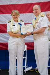 Rear Admiral William Chase, deputy director, command, control, communications, and computers/cyber, J6, joint staff, awards CDR Christina Hicks the Meritorious Service Medal for her service as Naval Computer and Telecommunications Station Guam Commanding Officer during her change of command ceremony on May 22.