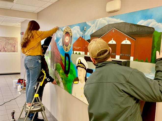 Student artist Haley Owens, on step-ladder at left, works on installing the three-panel mural at Starlite Fire Station No. 3 in April.
