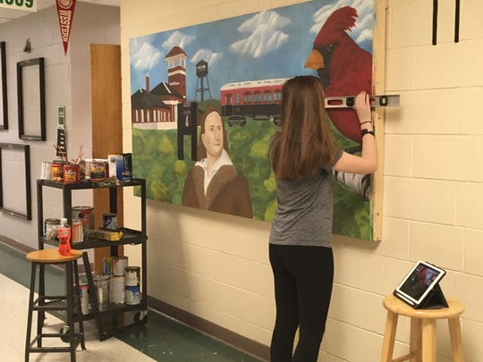"""Student artist Haley Owens, who will be a senior at Henderson County High School in the fall, works on the three-panel mural that now is installed at Starlite Fire Station No. 3 in the hallway at HCHS early last summer. The mural, which was installed at the fire station in April and is now """"framed"""", will be officially unveiled on Wednesday, May 29."""