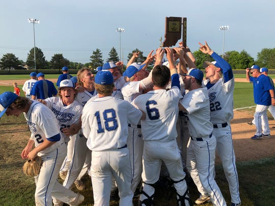 Hamilton Southeastern players lift the sectional trophy after defeating Carmel on Tuesday night.