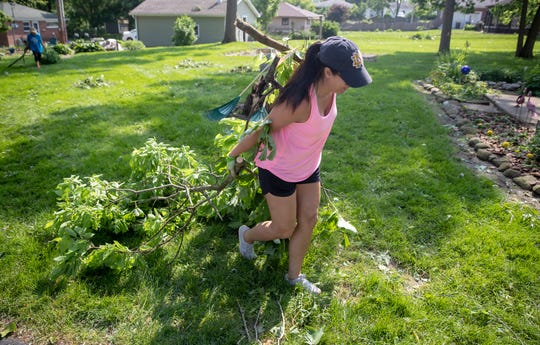 Ila Ellingwood moves branches from a fallen tree as she helps with cleanup after damage to Pendleton, where a tornado landed the previous evening, Tuesday, May 28, 2019. No injuries were reported, and property and tree damage were extensive in the area.