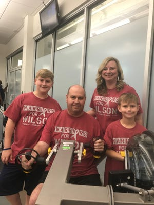 Mark and Brandi Wilson, and their sons Luke and Brett, at one of the machines Mark has used during his rehab to regain strength in his arm since brain surgery and cancer treatment.