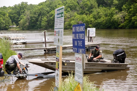 DNR officers remove a boat from the Tippecanoe River below the Norway Dam, Tuesday, May 28, 2019, in Monticello.