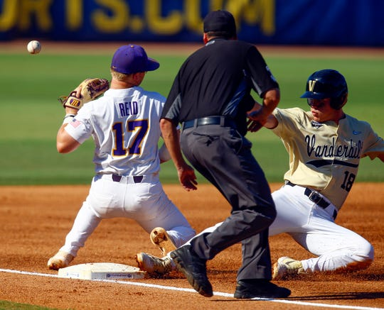 Vanderbilt's Pat DeMarco (18) slides safely into third base as LSU third baseman Chris Reid (17) misplays the ball during the second inning of an NCAA college baseball game at the Southeastern Conference tournament, Saturday, May 25, 2019, in Hoover, Ala. (AP Photo/Butch Dill)