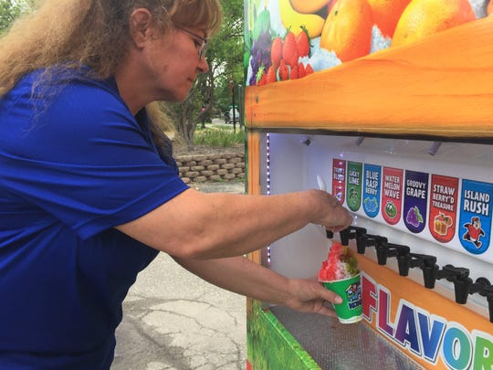 Stephanie Dunn demonstrates how customers of her and her husband's Kona Ice shaved ice food truck can choose and pour their own flavors, Tuesday, May 28, 2019.
