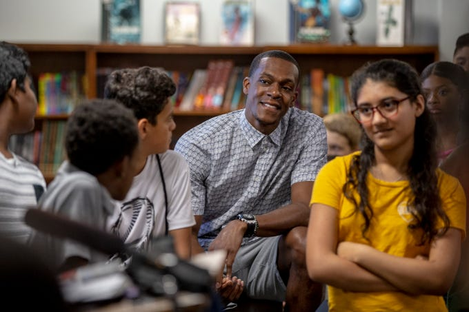 NBA basketball player and Louisville native, Rajon Rondo, listens to speakers at the Academy at Shawnee on Tuesday after the Rajon Rondo Foundation donated over $20,000 to fund the completion of a new middle school library. May 28, 2019