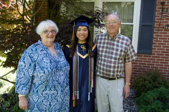 Zoe Halbeisen (center) with her adoptive parents Valli and Stephen Halbeisen of Charlotte when she graduated from Grand Ledge High School. Earlier this year she was reconnected with her birth parents in China, who have been looking for her for two decades.