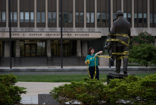 Anna Pegler-Gordon, a member of Reclaim MSU and professor at James Madison College, puts caution tape around the statue of John Hannah Tuesday morning, outside the John Hannah Administration building prior to the Board of Trustees meeting. A new president is expected to be named and voted in.  About ten minutes later, MSU Police had her remove the tape due to an ordinance violation.