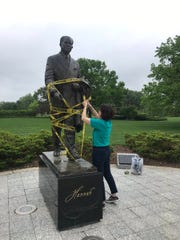 "Michigan State University Professor Anna Pegler-Gordon puts ""caution"" tape around the statue of former MSU President John Hannah near the Hannah Administration Building on Tuesday, May 28, 2019. She was protesting the secret search expected to conclude with the hiring of Dr. Samuel Stanley as MSU's next president."