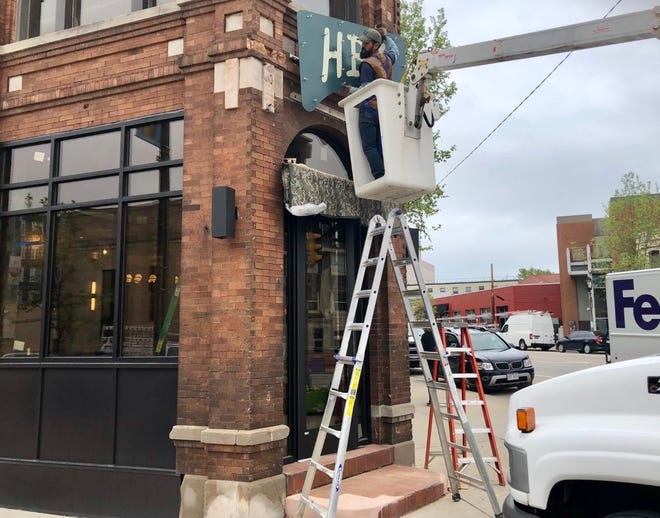 A worker installs the Hacienda Beer signs on the brewery's North Avenue taproom.