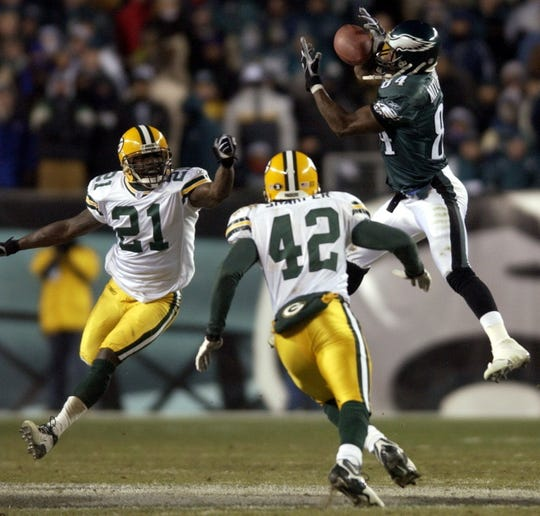 Philadelphia Eagles receiver Freddie Mitchell snares a pass for first down when it was fourth and 26 while being covered by Green Bay Packers Bhawoh Jue (21) and Darren Sharper late in the fourth quarter of their game Sunday, January 11, 2004 at Lincoln Financial Field in Philadelphia.