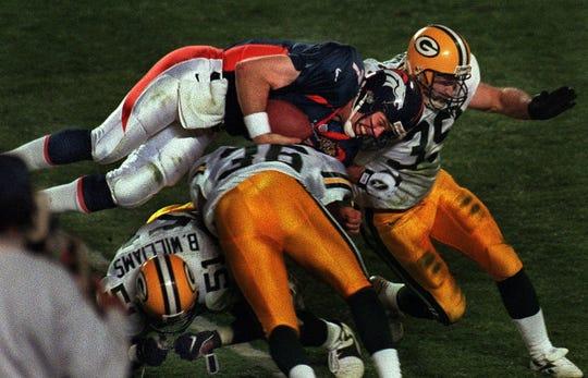Denver quarterback John Elway dives over Green Bay Packer defenders in the third quarter of the Super Bowl on January 25, 1998, in San Diego.